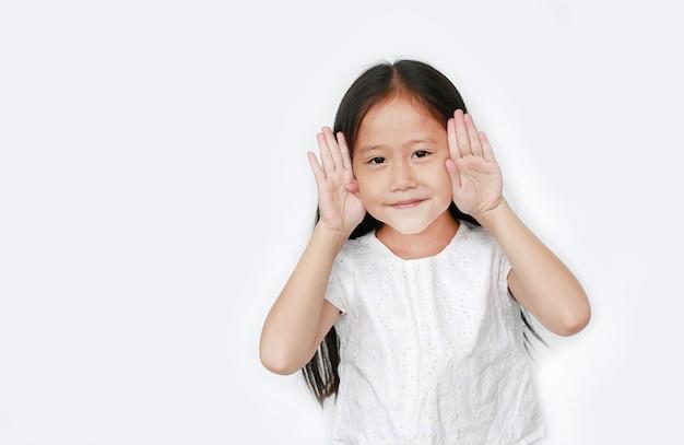 Gesti felici della ragazza del piccolo bambino che giocano peekaboo con lo spazio della copia. postura del bambino mani aperte dagli occhi con il sorriso.
