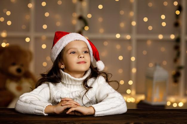 Felice bambina bambino in cappello della santa scrivendo la lista dei desideri o la lettera a babbo natale