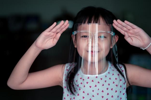 Ragazza felice del piccolo bambino con uno scudo di plastica per una maschera di protezione antivirus sul suo viso