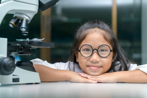 Sorriso felice del piccolo bambino e imparare nel laboratorio della scuola