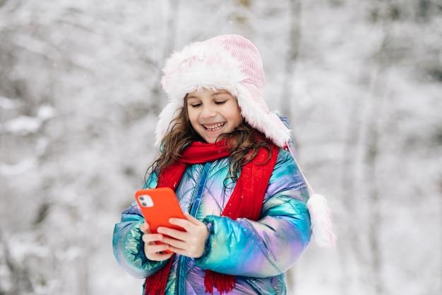 Il piccolo bambino felice usa l'app per la maschera facciale divertente dello smartphone guarda lo schermo del cellulare sorride a qualcosa di divertente.