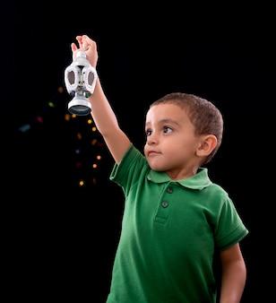 Felice piccolo bambino con la lanterna del ramadan
