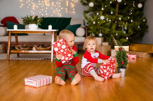 Piccoli bambini felici in pigiama che giocano con i regali di natale