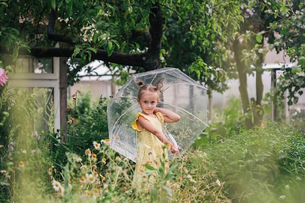 Felice bambina emotiva con ombrello trasparente in abito giallo e stivali da pioggia nell'estate del parco