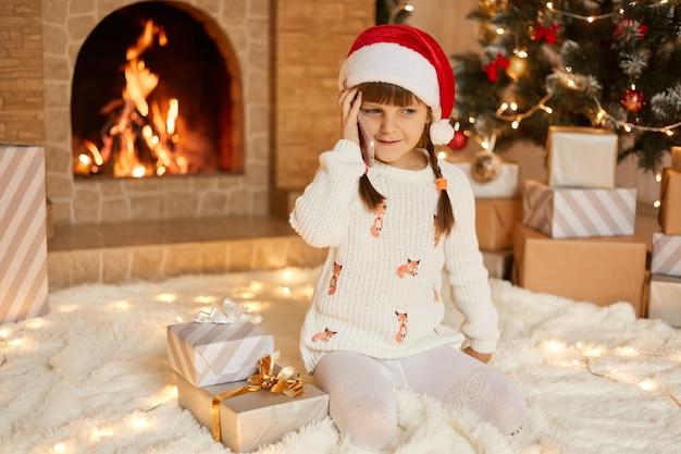Bambina felice in bellissimo maglione bianco e cappello rosso santa davanti all'albero di natale di capodanno