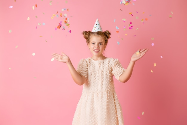 Felice bambina in un berretto di compleanno soffia via i suoi palmi coriandoli multicolori su uno sfondo rosa in studio