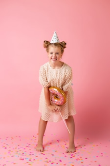 Una bambina felice in un berretto di compleanno tiene un palloncino a forma di ciambella su uno sfondo rosa in studio