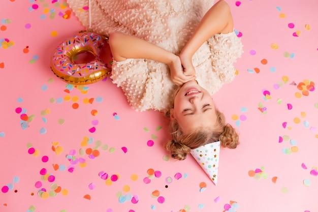 La bambina felice in un berretto di compleanno si trova tra i coriandoli multicolori su uno sfondo rosa