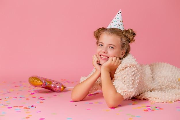 La bambina felice in un berretto di compleanno si trova su uno sfondo rosa con coriandoli, tiene le mani sul viso.