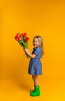 Felice bambina in un vestito blu e stivali di gomma sta lateralmente con un mazzo di tulipani rossi su una parete gialla con una copia dello spazio