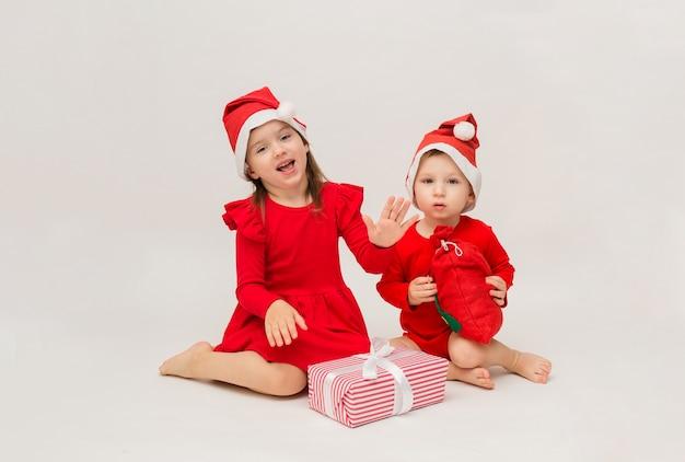 Felice bambina e ragazzo in berretti rossi con regali di natale sul muro bianco con spazio per il testo