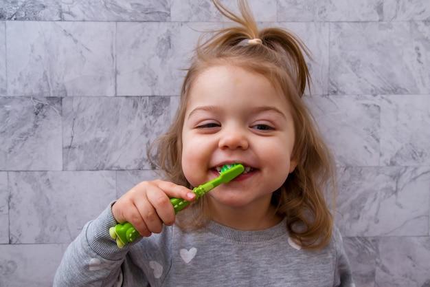La bambina felice si lava i denti in bagno. concetto di cure odontoiatriche