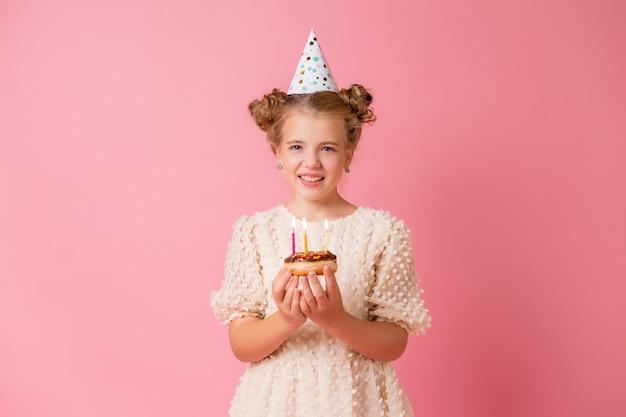 La bambina felice in un berretto per il suo compleanno esprime un desiderio e spegne le candeline su una torta.