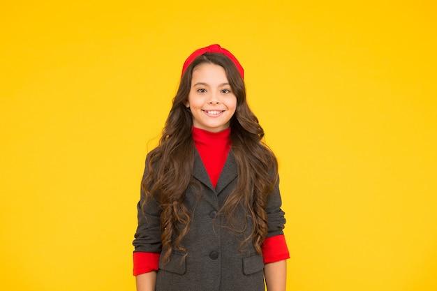 Sorriso felice del bambino della bambina in fondo giallo dell'uniforme della scuola, scolara.