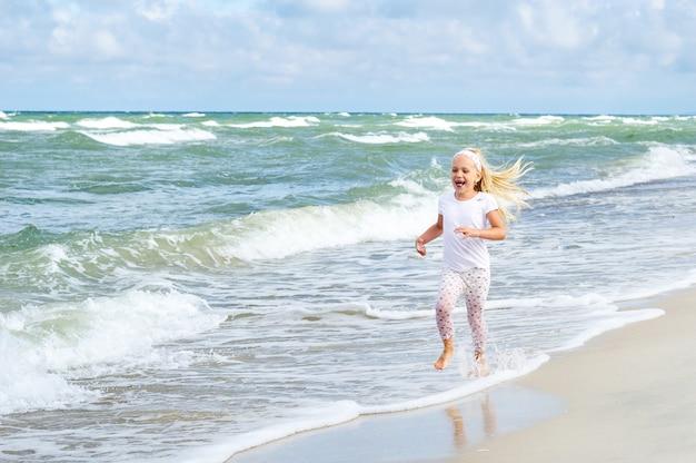Bambina felice in vestiti sulla spiaggia del mar baltico allo spiedo di curonian in lituania.