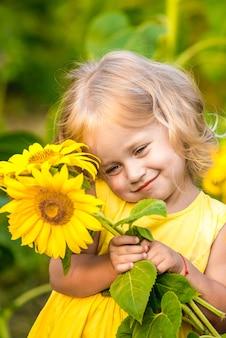 Bambina felice sul campo di girasoli in estate. bella bambina in girasoli