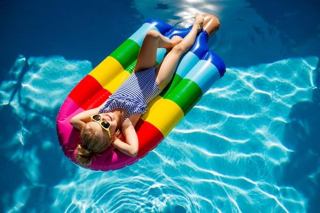 Bambina felice che galleggia su un materasso in piscina