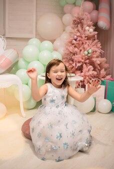 Una bambina felice con un vestito soffice è seduta sui cuscini nelle decorazioni del nuovo anno