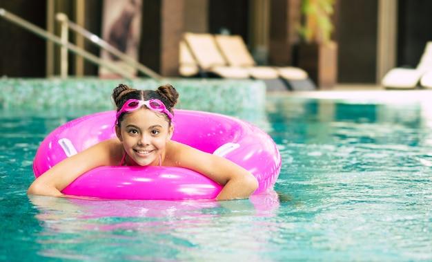 Bambina felice in occhiali che giocano con un anello gonfiabile rosa in piscina in una calda giornata estiva. i bambini imparano a nuotare. giocattoli d'acqua per bambini vacanza al mare in famiglia.