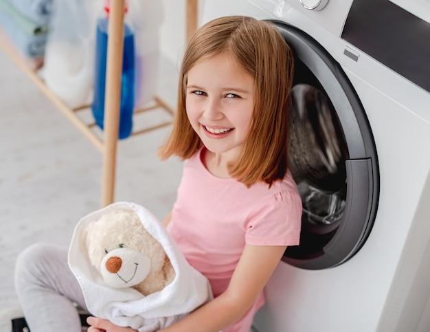 Bambina felice che abbraccia orsacchiotto in asciugamano dopo il lavaggio in lavatrice