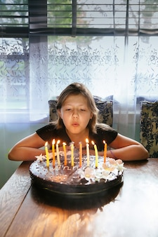 Bambina felice in casa con una torta di compleanno