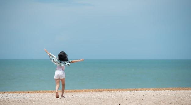 La bambina felice sorride alla grande e alza le braccia sopra la testa con gioia in vacanza in spiaggia sulla riva dell'oceano