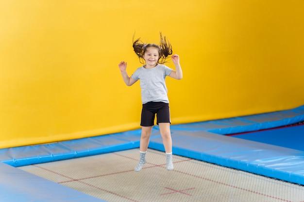 Bambina felice che salta sul trampolino nel centro fitness