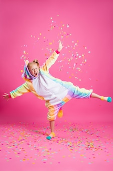 La bambina felice nell'unicorno di kigurumi su una parete rosa si rallegra in coriandoli multicolori