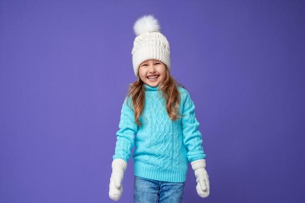 Bambina felice in un cappello lavorato a maglia
