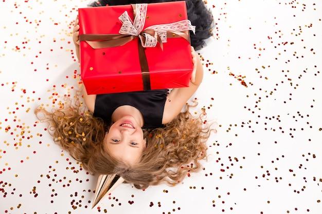 Una bambina felice si trova su uno sfondo bianco con una confezione regalo e un berretto per il suo compleanno.