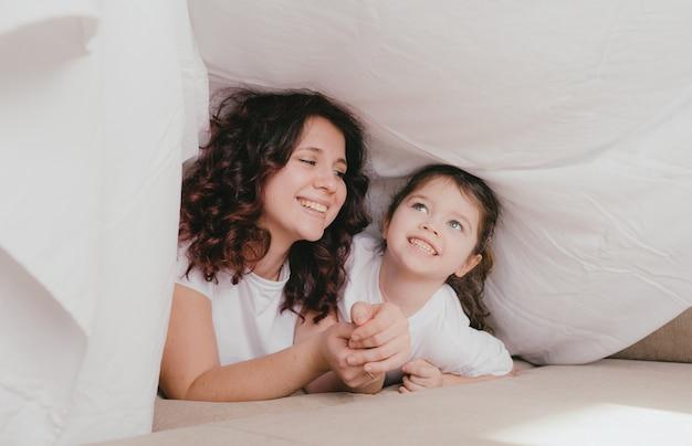 Una bambina felice in un dolcevita leggero abbraccia sua madre sotto un lenzuolo bianco. una madre amorevole e premurosa