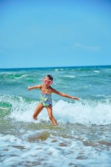 Bambina felice nella maschera per il nuoto che corre e che salta tra le onde
