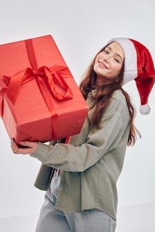 Regalo felice del nuovo anno della bambina nella casella rossa delle mani
