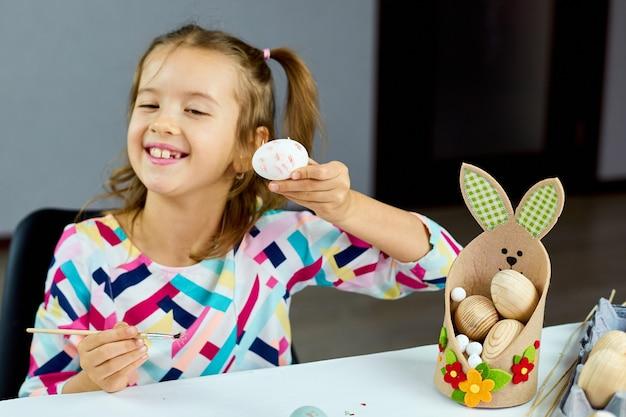 Pittura felice della bambina, disegno con le uova della spazzola a casa. bambino che prepara per la pasqua, divertirsi e celebrare la festa. buona pasqua, fai da te Foto Premium