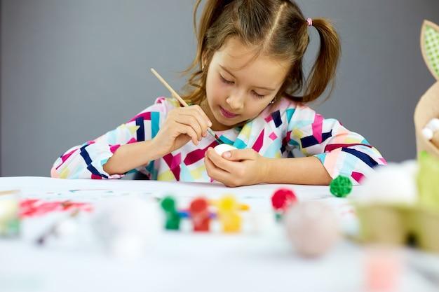 Pittura felice della bambina, disegno con le uova della spazzola a casa. bambino che prepara per la pasqua, divertirsi e celebrare la festa. buona pasqua, fai da te