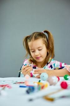 Pittura felice della bambina, disegno con le uova della spazzola a casa