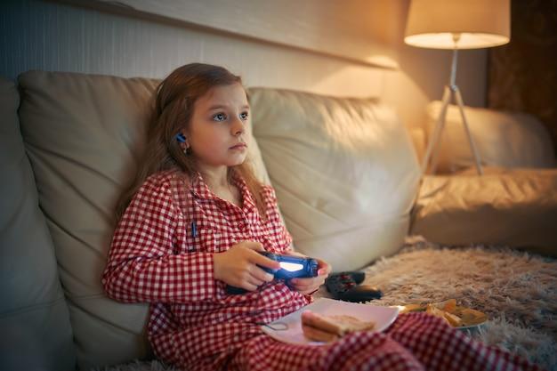 Bambina felice in pigiami che si siede sul sofà, che mangia pizza e che gioca i video giochi con la leva di comando a casa.