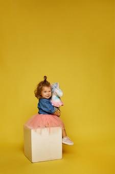Bambina felice in gonna rosa e giacca di jeans con un cavallo giocattolo sopra il muro giallo
