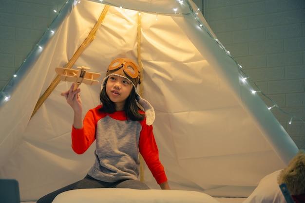 Bambina felice che gioca in tenda a casa, bambino adorabile divertente divertendosi nella stanza dei bambini.