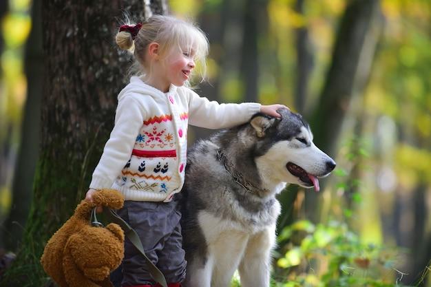 Bambina felice che gioca con il grande cane in giardino.