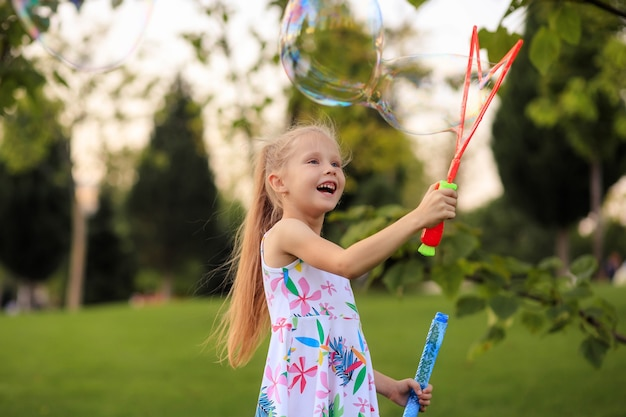 Bambina felice che gioca con le bolle di sapone di estate nel parco.