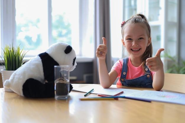 L'allievo felice della bambina studia online a casa, il bambino piccolo sorridente mostra il pollice in su raccomanda la lezione o la lezione.
