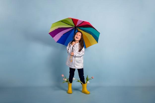 Una bambina felice con un impermeabile e stivali di gomma gialli con fiori tiene un ombrello multicolore su uno sfondo blu con una copia dello spazio