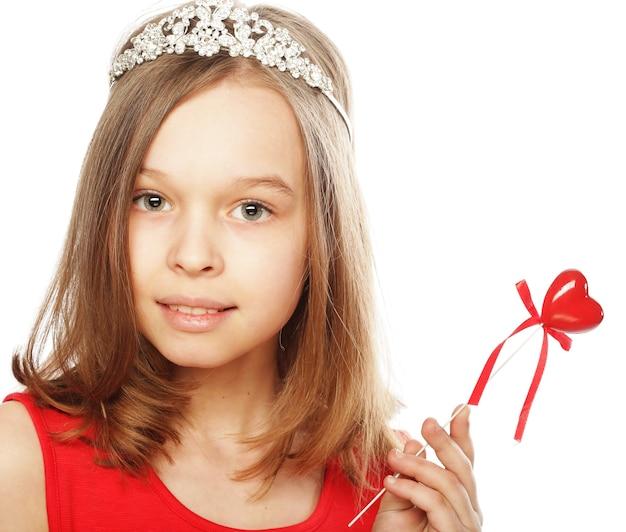 Bambina felice in vestito rosso con cuore rosso su bianco