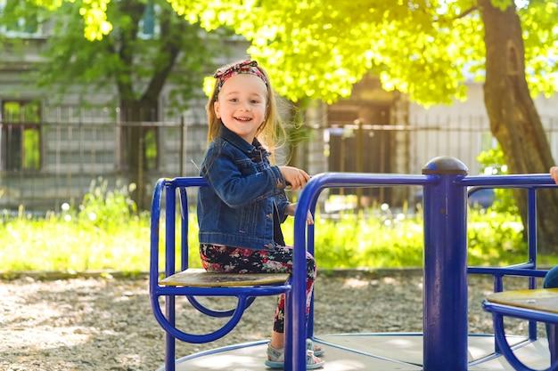 La bambina felice che guida sul allegro va in giro nel parco giochi per bambini all'aperto nel parco