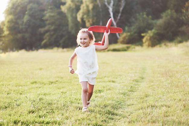 Bambina felice che corre sul campo con un aereo giocattolo rosso in mano
