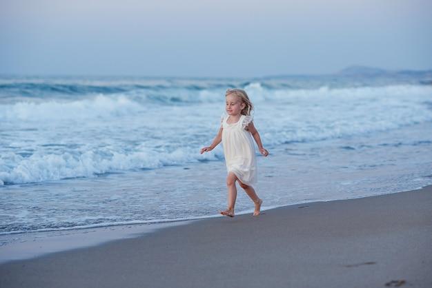 Bambina felice che corre e salta in spiaggia