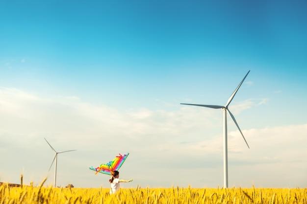 Bambina felice che corre in un campo di grano con un aquilone in estate