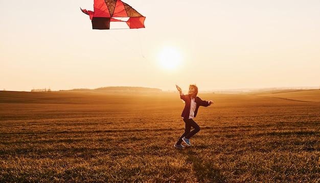 Bambina felice che funziona con l'aquilone in mano sul bellissimo campo a tempo sunrishe