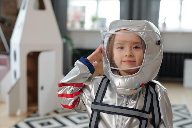 Bambina felice in tuta spaziale in piedi nel soggiorno